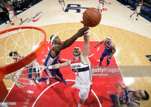 Joel Embiid of the Philadelphia 76ers and Marcin Gortat of the Washington Wizards fight for the rebound on October 18 2017 at Capital One Arena in...