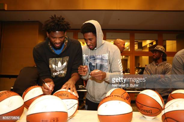 Joel Embiid of the Philadelphia 76ers and Rondae HollisJefferson of the Brooklyn Nets signs balls during the Basketball Without Borders Africa...