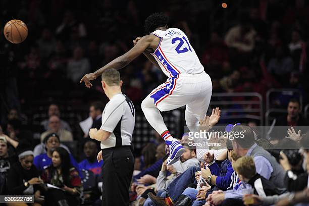 Joel Embiid of the Philadelphia 76ers can't make a save as he crashes onto the crowd during the fourth quarter against the Brooklyn Nets at the Wells...