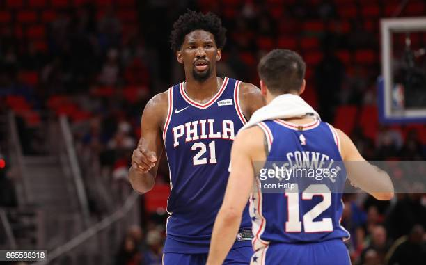 Joel Embiid of the Philadelphia 76ers celebrates a win over the Detroit Pistons with teammate TJ McConnell during the NBA game at Little Caesars...