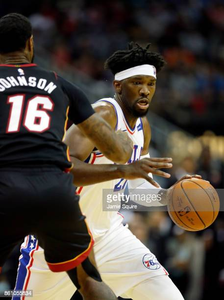 Joel Embiid of the Philadelphia 76ers controls the ball as James Johnson of the Miami Heat defends during the game at Sprint Center on October 13...
