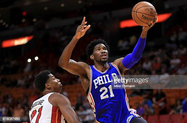Joel Embiid of the Philadelphia 76ers drives on Hassan Whiteside of the Miami Heat during a preseason game at American Airlines Arena on October 21...