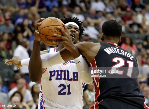 Joel Embiid of the Philadelphia 76ers drives toward the basket as Hassan Whiteside of the Miami Heat of the Miami Heat defends during the game at...