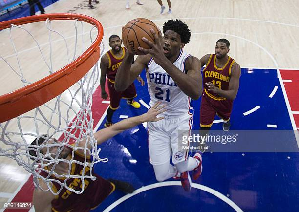 Joel Embiid of the Philadelphia 76ers goes up for a shot against Kevin Love and Tristan Thompson of the Cleveland Cavaliers in the first quarter at...
