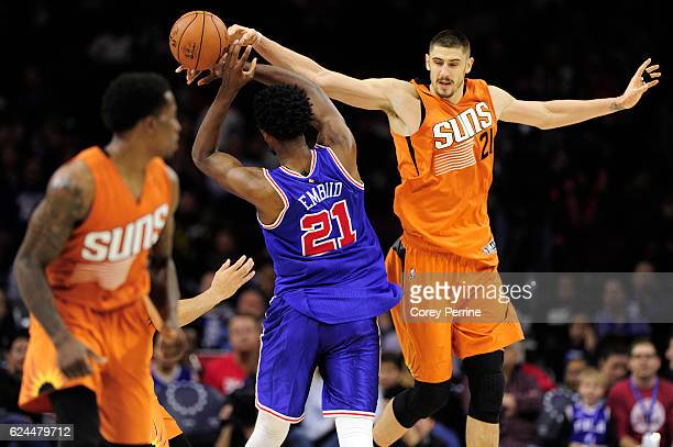 Joel Embiid of the Philadelphia 76ers is fouled by Alex Len of the Phoenix Suns during the fourth quarter at the Wells Fargo Center on November 19...