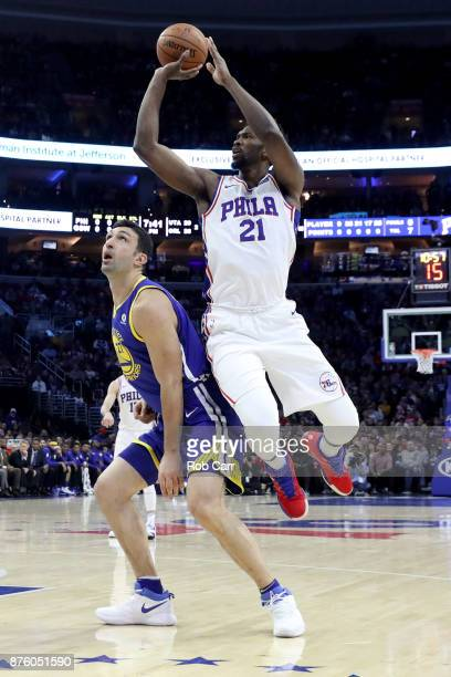 Joel Embiid of the Philadelphia 76ers puts up a shot over Zaza Pachulia of the Golden State Warriors in the first half at Wells Fargo Center on...