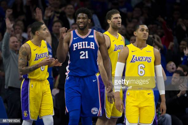 Joel Embiid of the Philadelphia 76ers reacts in front of Kyle Kuzma Brook Lopez and Jordan Clarkson of the Los Angeles Lakers after Ben Simmons made...