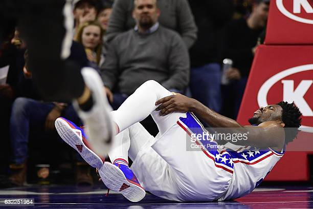 Joel Embiid of the Philadelphia 76ers tweaks his leg after landing on it awkwardly after a dunk on the Portland Trail Blazers during the third...