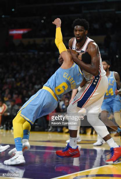 Joel Embiid of the Philadelphia 76ers wraps up Jordan Clarkson of the Los Angeles Lakers and is called with a foul during the first half of the...