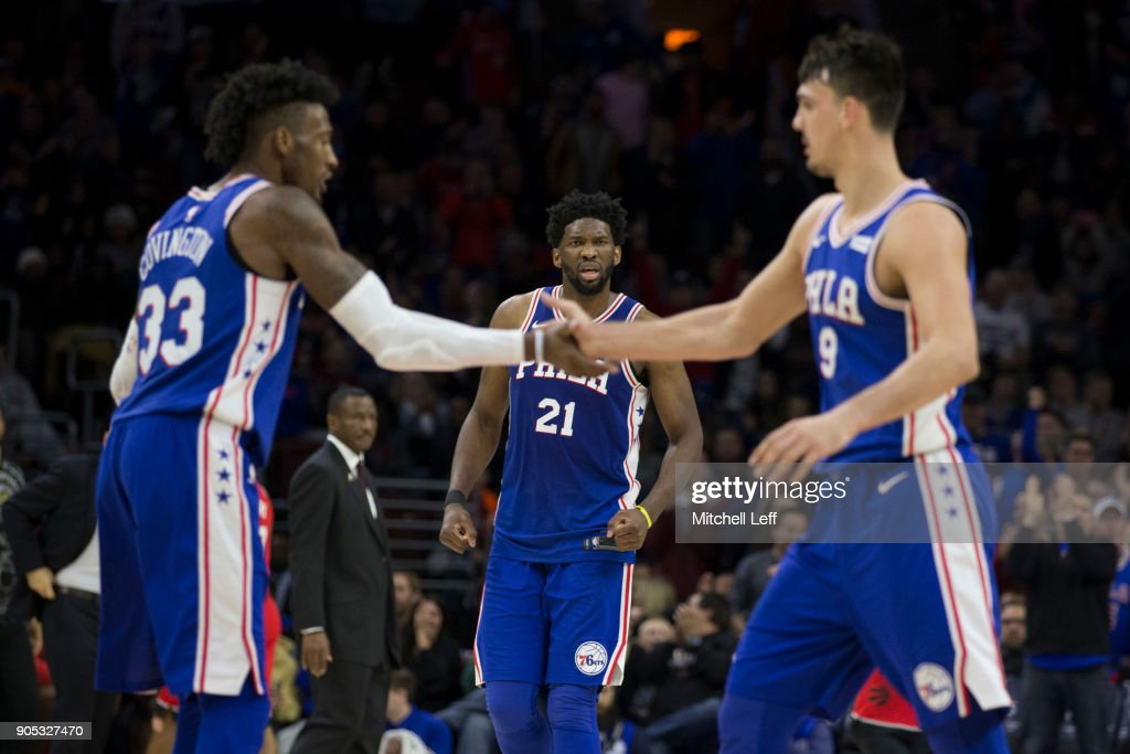 Joel Embiid #21, Robert Covington #33, and Dario Saric #9 of the Philadelphia 76ers celebrate in the fourth quarter against the Toronto Raptors at the Wells Fargo Center on January 15, 2018 in Philadelphia, Pennsylvania. The 76ers defeated the Raptors 117-111.