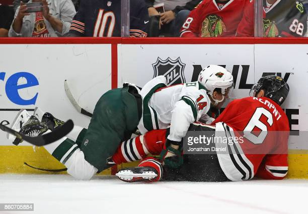 Joel Eriksson Ek of the Minnesota Wild lands on top of Michal Kempny of the Chicago Blackhawks as they battle for the puck at the United Center on...