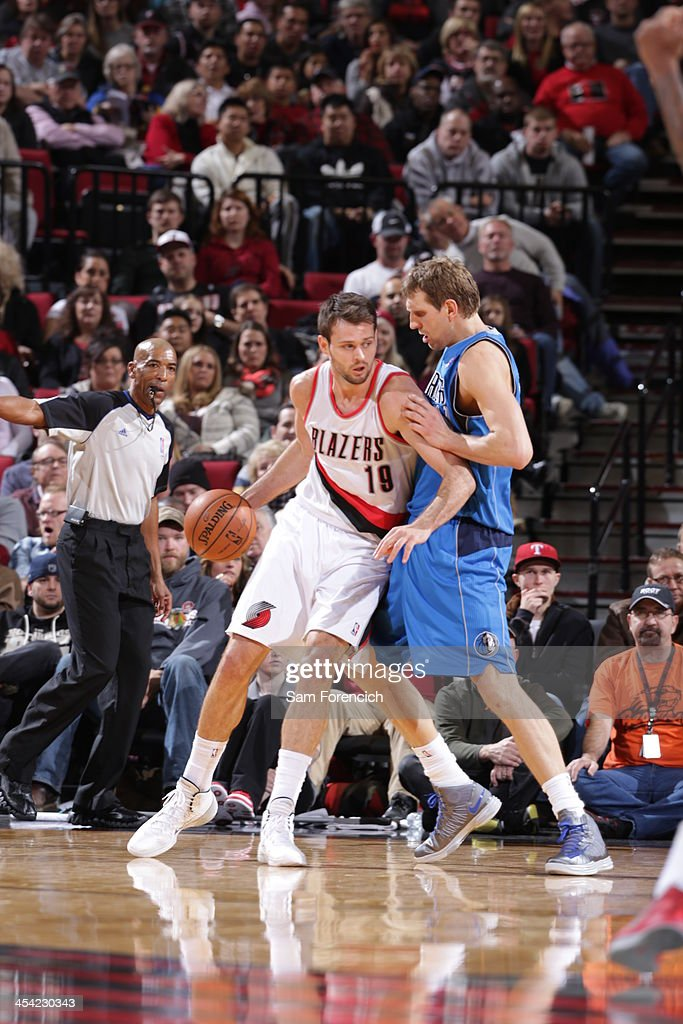 Joel Freeland of the Portland Trail Blazers controls the ball against Dirk Nowitzki of the Dallas Mavericks on December 7 2013 at the Moda Center...