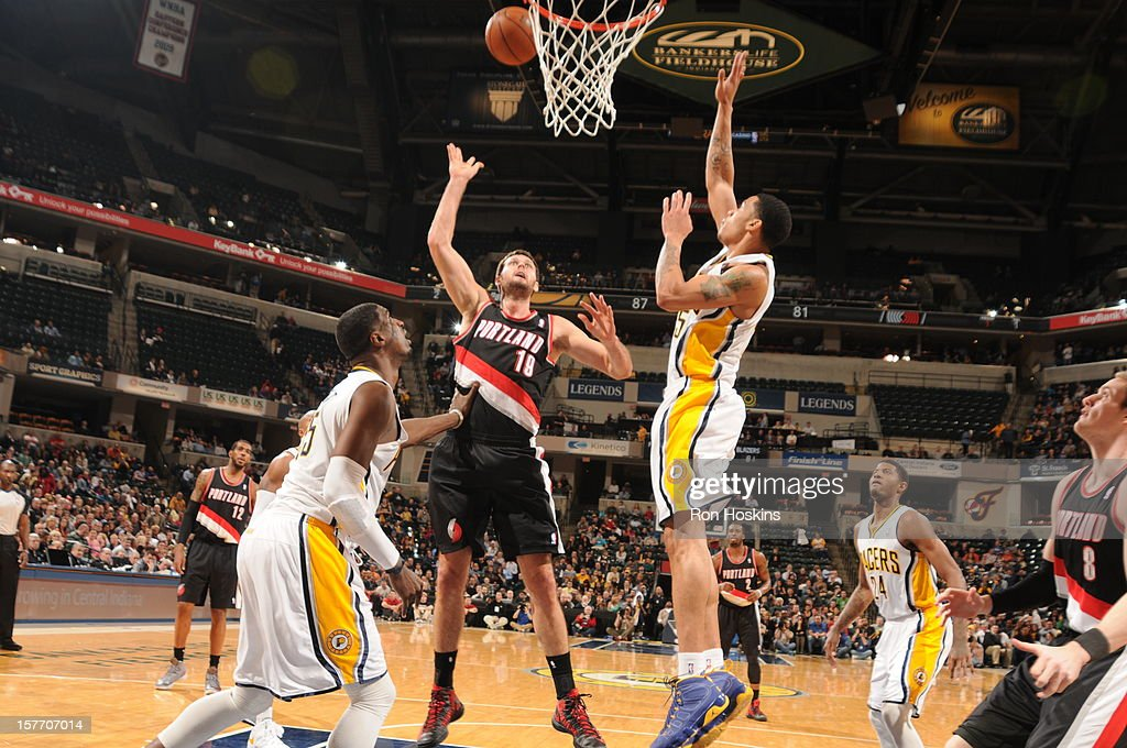 <a gi-track='captionPersonalityLinkClicked' href=/galleries/search?phrase=Joel+Freeland&family=editorial&specificpeople=757235 ng-click='$event.stopPropagation()'>Joel Freeland</a> #19 of the Portland Trail Blazers shoots the ball against <a gi-track='captionPersonalityLinkClicked' href=/galleries/search?phrase=Gerald+Green&family=editorial&specificpeople=644655 ng-click='$event.stopPropagation()'>Gerald Green</a> #25 and <a gi-track='captionPersonalityLinkClicked' href=/galleries/search?phrase=Roy+Hibbert&family=editorial&specificpeople=725128 ng-click='$event.stopPropagation()'>Roy Hibbert</a> #55 of the Indiana Pacers on December 5, 2012 at Bankers Life Fieldhouse in Indianapolis, Indiana.