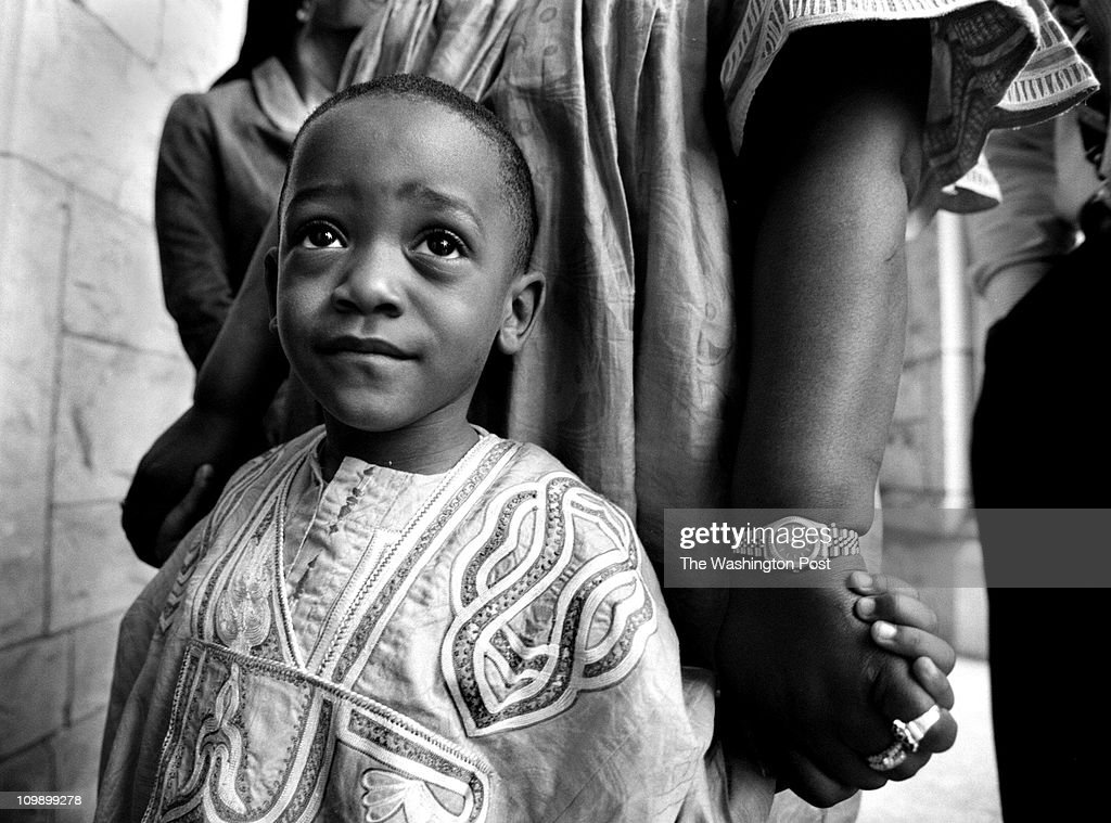 04/12/98 Joel Gnansounou of Woodbridge VA dressed in traditional Benin clothes holds the hand of his mother as they wait to enter St Augustine Church...