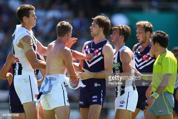 Joel Hamling of the Dockers wrestles with Mason Cox and Will HoskinElliott of the Magpies during the 2017 JLT Community Series AFL match between the...