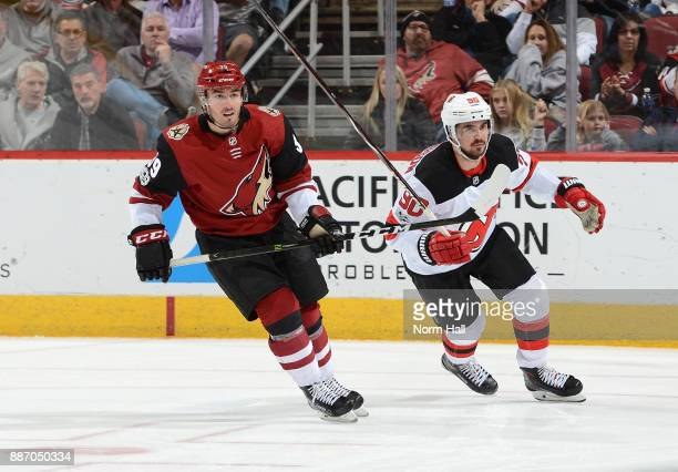 Joel Hanley of the Arizona Coyotes skates up ice with Marcus Johansson of the New Jersey Devils at Gila River Arena on December 2 2017 in Glendale...