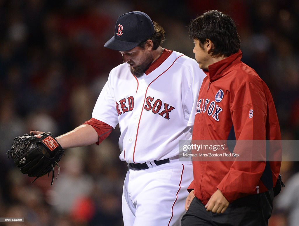 Joel Hanrahan #52 of the Boston Red Sox looks at his arm while walking off the field with trainer Masai Takahashi after giving up a lead against the Minnesota Twins in the ninth inning on May 6, 2013 at Fenway Park in Boston, Massachusetts.