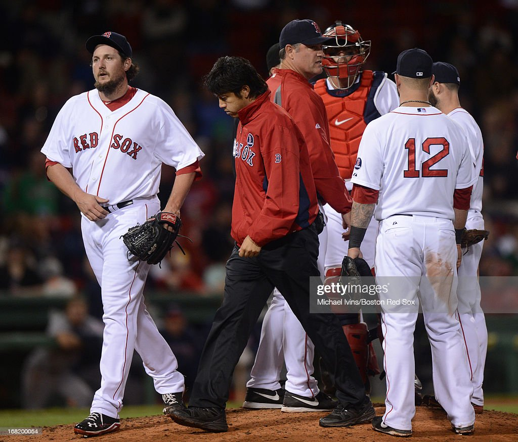 Joel Hanrahan of the Boston Red Sox walks off the field with trainer Masai Takahashi after giving up a lead against the Minnesota Twins in the ninth...
