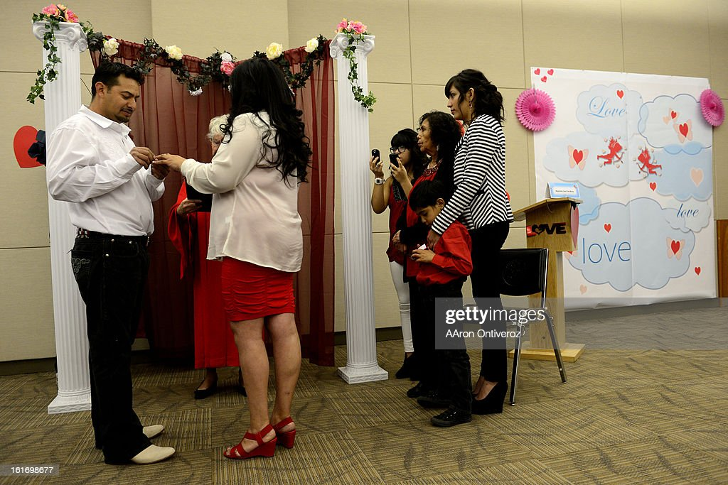 Joel Herrera places a ring on the finger of Sylvenvestra Rodriguez during a Valentine's Day marriage celebration at the Denver Clerk and Recorder's office. Couples applying for marriage licenses received gift bags containing gift certificates to local restaurants among other treats to celebrate their union.