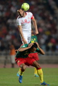 Joel Job Matip of Cameroon battles with Yassin Chikhaoui of Tunisia during the FIFA 2014 World Cup qualifier at the Stade Olympique de Radès on...