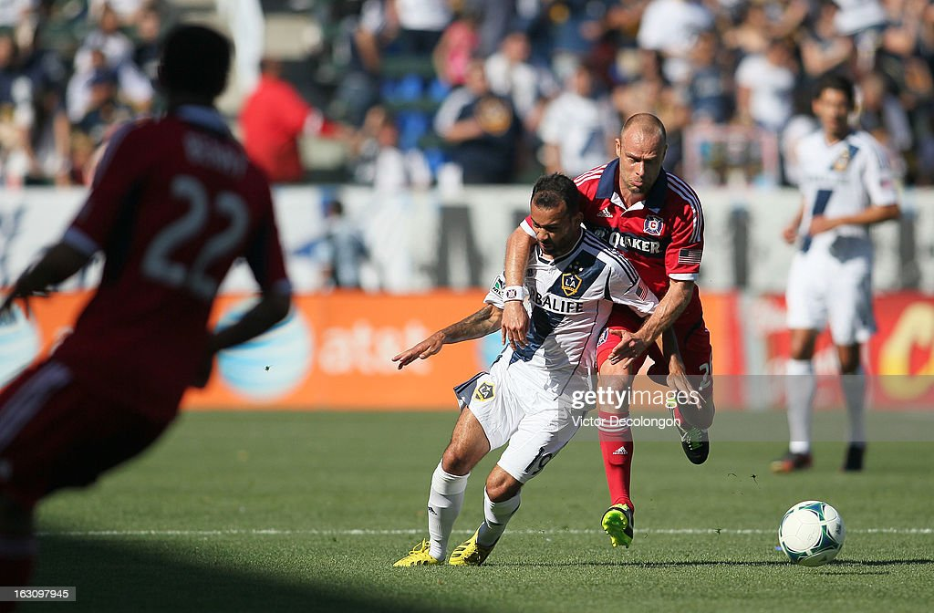 Joel Lindpere #26 of the Chicago Fire makes contact with Juninho #19 of the Los Angeles Galaxy during the MLS match at The Home Depot Center on March 3, 2013 in Carson, California. The Galaxy defeated the Fire 4-0.