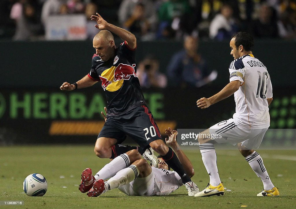 Joel Lindpere #20 of the New York Red Bulls is tackled by <a gi-track='captionPersonalityLinkClicked' href=/galleries/search?phrase=Omar+Gonzalez&family=editorial&specificpeople=2488485 ng-click='$event.stopPropagation()'>Omar Gonzalez</a> #4 of the Los Angeles Galaxy as <a gi-track='captionPersonalityLinkClicked' href=/galleries/search?phrase=Landon+Donovan&family=editorial&specificpeople=171601 ng-click='$event.stopPropagation()'>Landon Donovan</a> #10 of the Galaxy looks on in the second half at The Home Depot Center on May 7, 2011 in Carson, California. The Red Bulls and Galaxy played to a 1-1 draw.