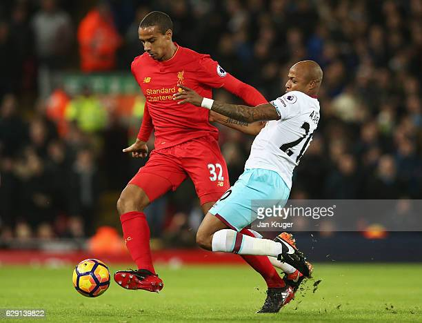 Joel Matip of Liverpool and Andre Ayew of West Ham United compete for the ball during the Premier League match between Liverpool and West Ham United...