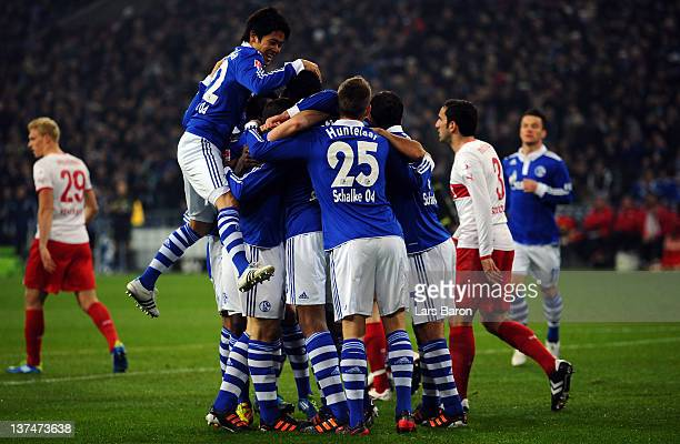 Joel Matip of Schalke celebrates with Atsuto Uchida and other team mates after scoring his teams first goal during the Bundesliga match between FC...