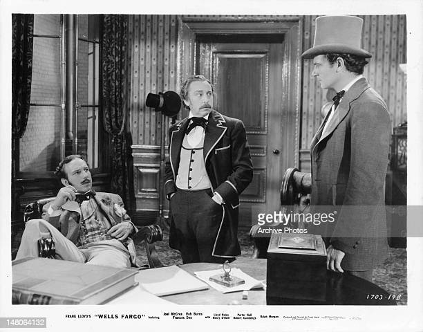 Joel McCrea wearing a top hat and talking with two other men in a scene from the film 'Wells Fargo' 1937