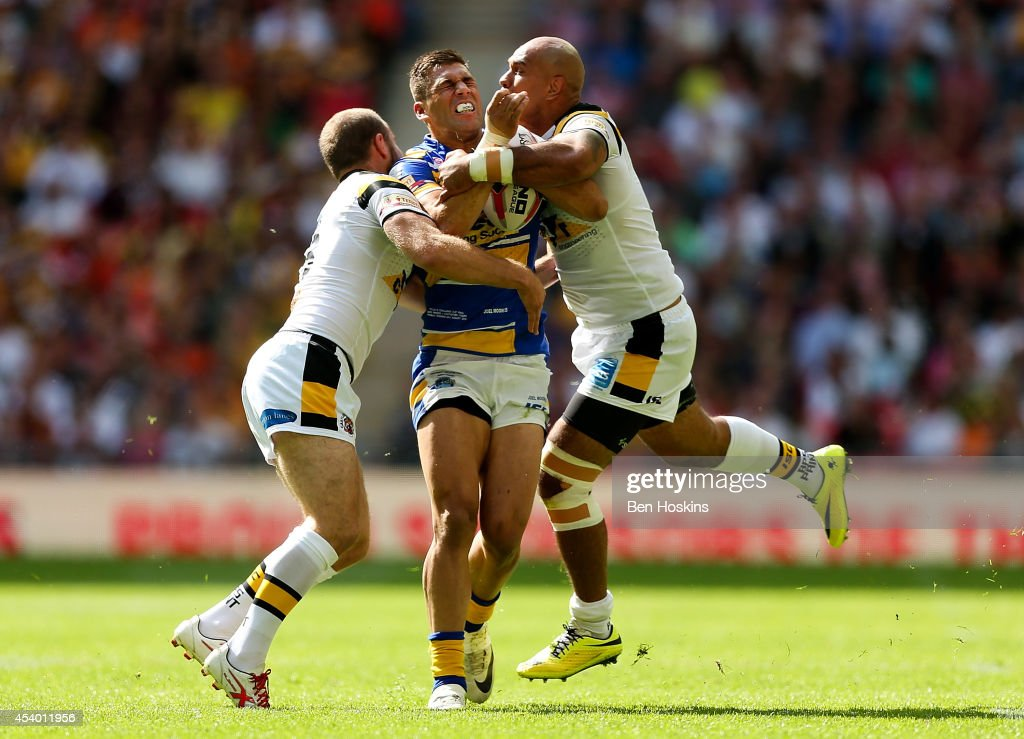 Joel Moon of Leeds is tackled by Liam Finn (L) and Jake Webster (R) of Castleford during the Tetley's Challenge Cup Final between Leeds Rhinos and Castleford Tigers at Wembley Stadium on August 23, 2014 in London, England.