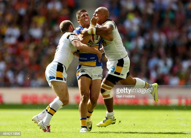 Joel Moon of Leeds is tackled by Liam Finn and Jake Webster of Castleford during the Tetley's Challenge Cup Final between Leeds Rhinos and Castleford...
