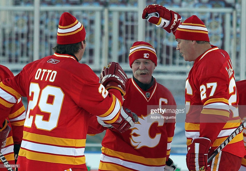 Joel Otto #29 (L) and Brian MacLellan #27 (R) congratulate Lanny McDonald #9 (C) of the Calgary Flames Alumni on his penalty shot goal against the Montreal Canadiens Alumni during the Alumni game held as part of the 2011 NHL Heritage Classic festivities at McMahon Stadium on February 19, 2011 in Calgary, Alberta, Canada.