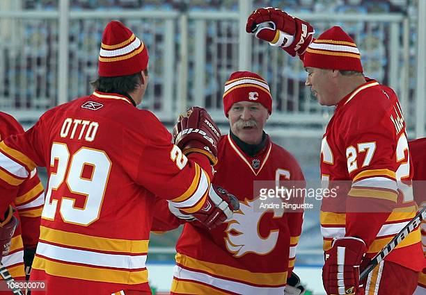 Joel Otto and Brian MacLellan congratulate Lanny McDonald of the Calgary Flames Alumni on his penalty shot goal against the Montreal Canadiens Alumni...