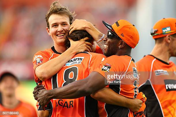 Joel Paris and Michael Carberry of the Scorchers congratulate Ashton Agar after taking a catch to dismiss Brad Hodge of the Strikers during the Big...