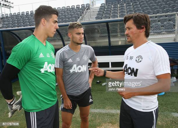 Joel Pereira and Andreas Pereira of Manchester United talk to Assistant Manager Rui Faria during a first team training session as part of their...