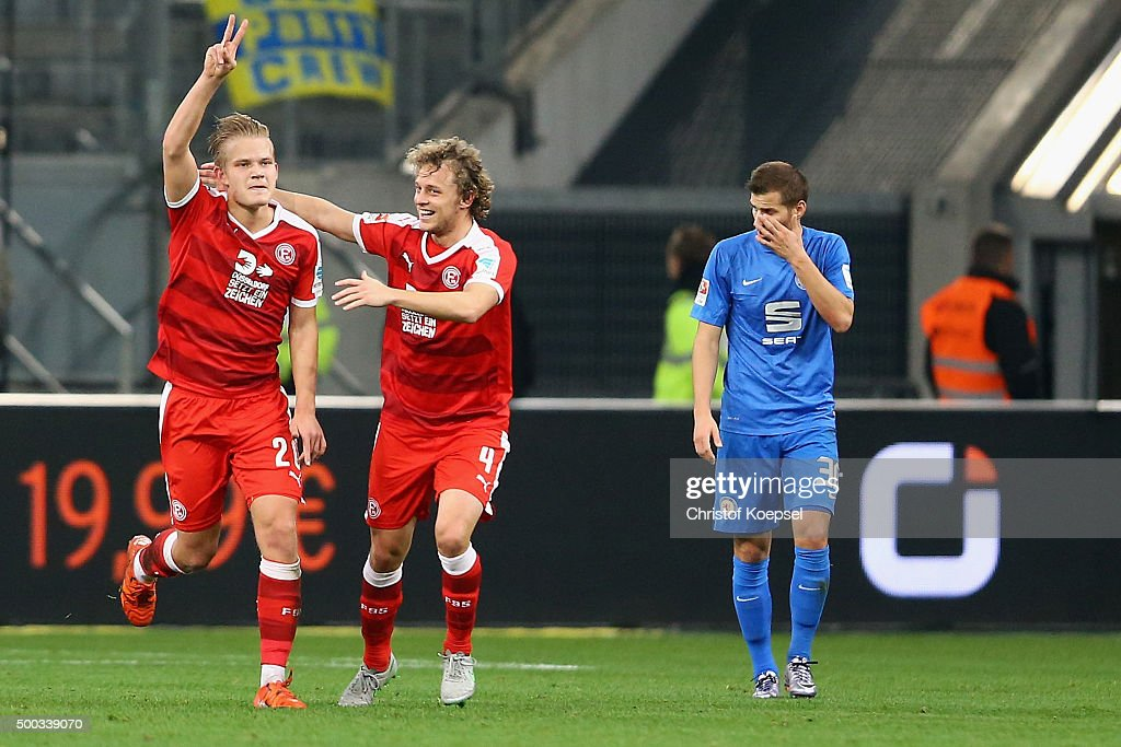 Joel Pohjanpalo of Duesseldorf celebrates the first goal with Julian Schauerte of Duesseldorf and Hendrick Zuck of Braunschweig looks dejected during...