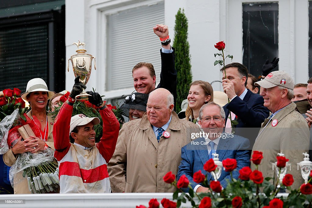Joel Rosario atop Orb celebrates with the trophy after winning the 139th running of the Kentucky Derby as trainer Shug McGaughey (2nd-R) looks on at Churchill Downs on May 4, 2013 in Louisville, Kentucky.