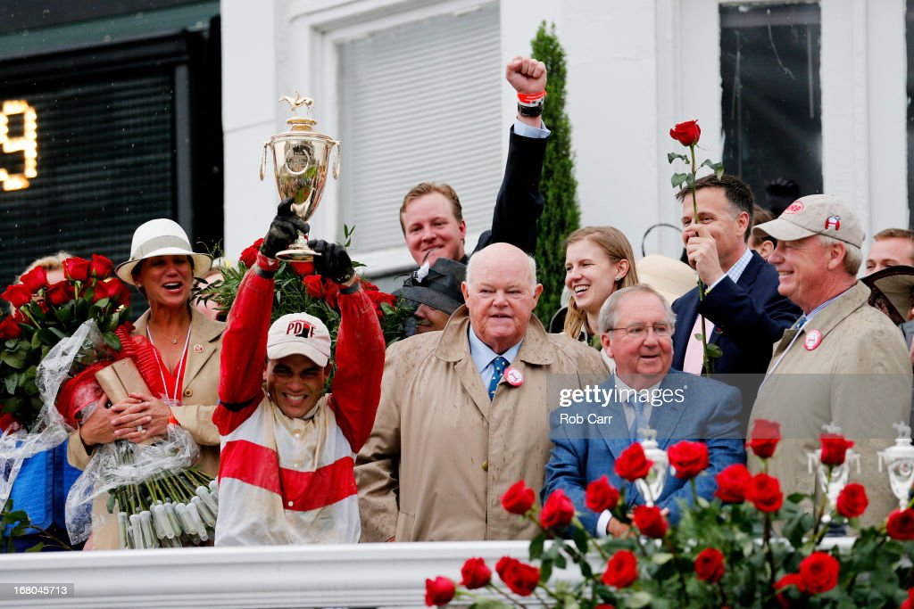 "Joel Rosario atop Orb celebrates with the trophy after winning the 139th running of the Kentucky Derby as owner Ogden ""Dinny"" Phipps , trainer Shug McGaughey and owner Stuart Janney III look on at Churchill Downs on May 4, 2013 in Louisville, Kentucky."