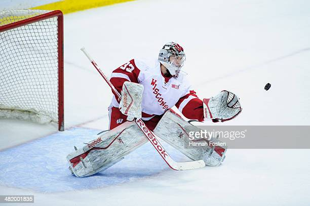 Joel Rumpel of the Wisconsin Badgers makes a glove side save during the semifinal game of the Big Ten Men's Ice Hockey Championship against the Penn...