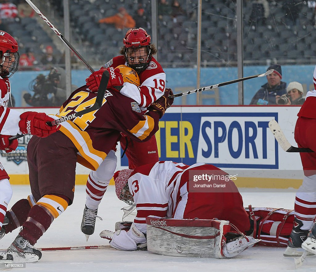 Joel Rumpel #33 of the Wisconsin Badgers makes a save as teammate Jake McCabe #19 grabs Zach Budish #24 of the Minnesota Golden Gophers during the Hockey City Classic at Soldier Field on February 17, 2013 in Chicago, Illinois.