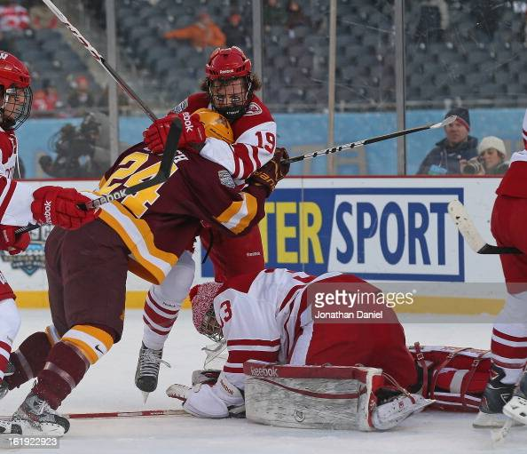 Joel Rumpel of the Wisconsin Badgers makes a save as teammate Jake McCabe grabs Zach Budish of the Minnesota Golden Gophers during the Hockey City...