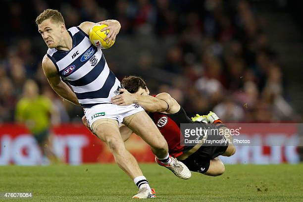 Joel Selwood of the Cats breaks the tackle of Ben Howlett of the Bombers during the round 10 AFL match between the Essendon Bombers and the Geelong...