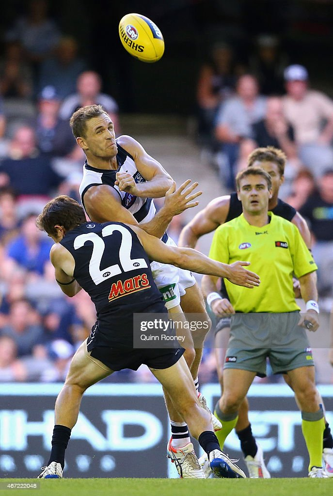 Joel Selwood of the Cats handballs whilst being tackled by Jason Tutt of the Blues during the NAB Challenge AFL match between the Carlton Blues and the Geelong Cats at Etihad Stadium on March 22, 2015 in Melbourne, Australia.