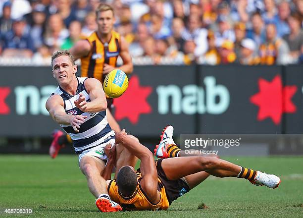 Joel Selwood of the Cats handballs whilst being tackled by Josh Gibson of the Hawks during the round one AFL match between the Hawthorn Hawks and the...
