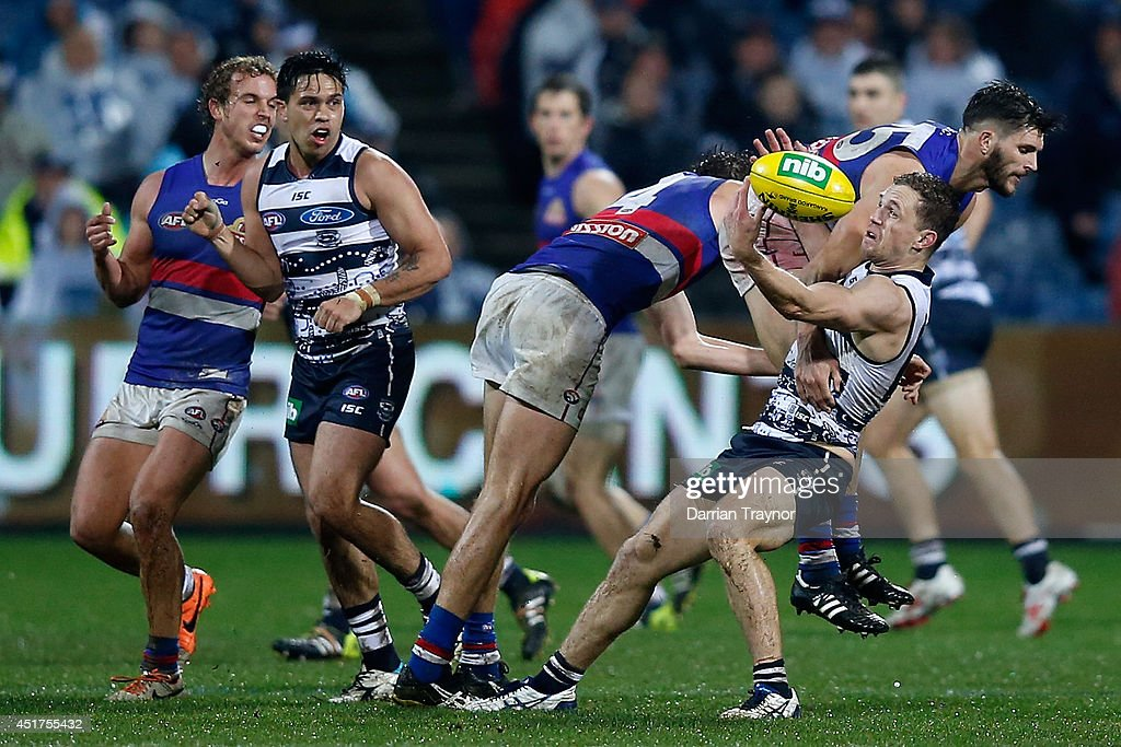 Joel Selwood of the Cats is hit by Koby Stevens of the Bulldogs during the round 16 AFL match between the Geelong Cats and the Western Bulldogs at Skilled Stadium on July 6, 2014 in Melbourne, Australia.