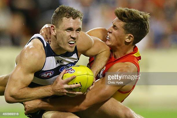Joel Selwood of the Cats is tackled by David Swallow of the Suns during the round 14 AFL match between the Gold Coast Suns and the Geelong Cats at...