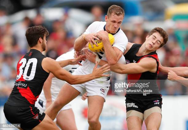 Joel Selwood of the Cats is tackled by Kyle Langford and Zach Merrett of the Bombers during the AFL 2017 JLT Community Series match between the...