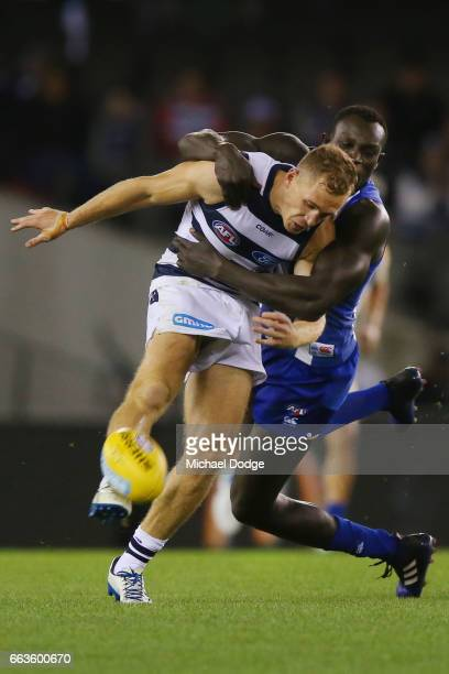 Joel Selwood of the Cats is tackled by Majak Daw of the Kangaroos during the round two AFL match between the Geelong Cats and the North Melbourne...