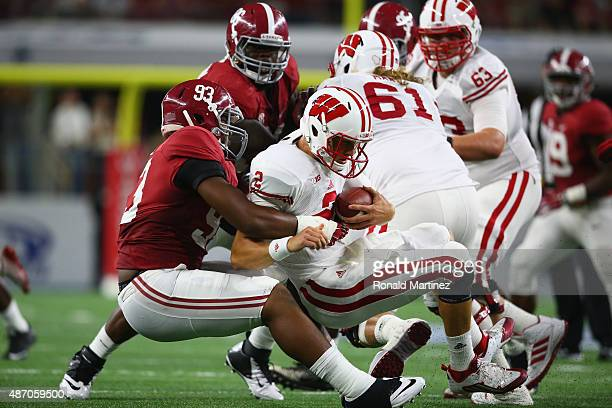 Joel Stave of the Wisconsin Badgers is sacked by Jonathan Allen of the Alabama Crimson Tide in the second quarter during the Advocare Classic at ATT...