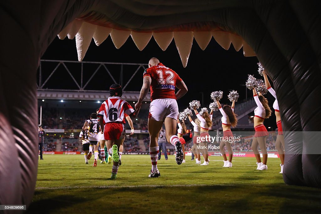 Joel Thompson of the Dragons runs out with a local junior footballer during the round 12 NRL match between the St George Illawarra Dragons and the North Queensland Cowboys at WIN Jubilee Stadium on May 28, 2016 in Wollongong, Australia.